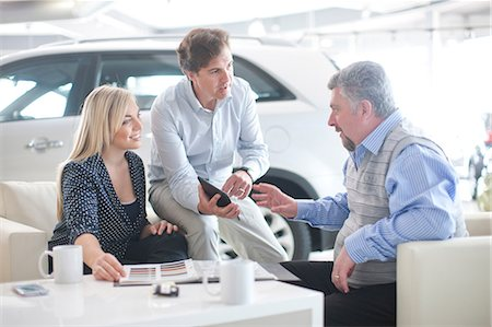 Car salesman talking to couple in car showroom Stock Photo - Premium Royalty-Free, Code: 649-07119148