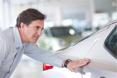 Mid adult man examining car in showroom Stock Photo - Premium Royalty-Free, Code: 649-07119154
