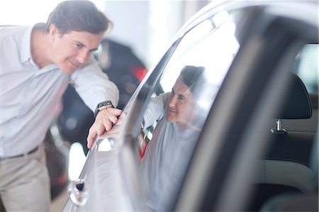 Mid adult man looking at car in showroom Stock Photo - Premium Royalty-Free, Code: 649-07119155