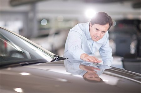 Mid adult man looking at car bonnet in showroom Stock Photo - Premium Royalty-Free, Code: 649-07119156