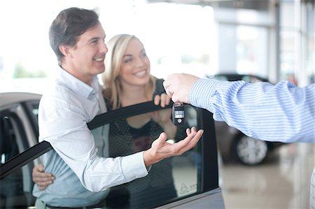 Car salesman handing key to couple in showroom Stock Photo - Premium Royalty-Free, Code: 649-07119153