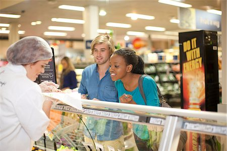 Young sales assistant at counter with customers Stock Photo - Premium Royalty-Free, Code: 649-07119164