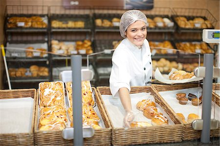 Young sales assistant holding sweet pastries Stock Photo - Premium Royalty-Free, Code: 649-07119160