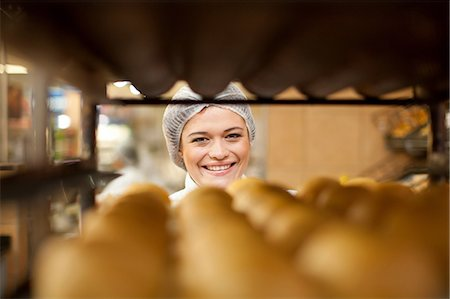 Portrait of young baker and tray of bread rolls Stock Photo - Premium Royalty-Free, Code: 649-07119162