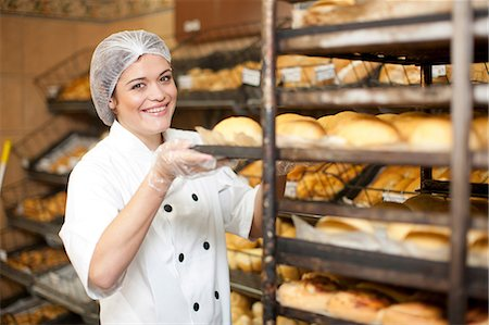Portrait of young baker holding tray of bread rolls Stock Photo - Premium Royalty-Free, Code: 649-07119163