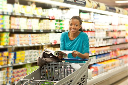 Female shopper with brochure in supermarket Stock Photo - Premium Royalty-Free, Code: 649-07119179