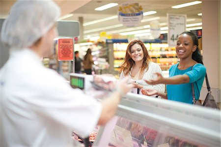 Young male sales assistant serving customers at counter Stock Photo - Premium Royalty-Free, Code: 649-07119171