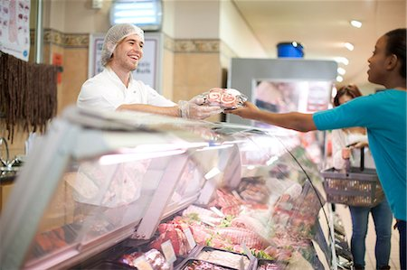 Young male sales assistant serving customer at counter Stock Photo - Premium Royalty-Free, Code: 649-07119172