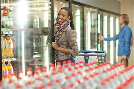 reaching - Female shopper reaching for soft drink from cooler Stock Photo - Premium Royalty-Free, Code: 649-07119185