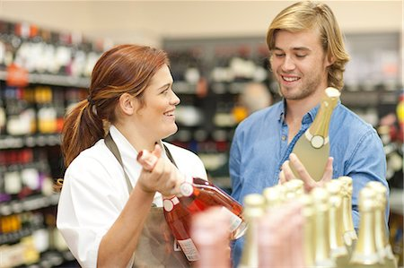 Female shop assistant advising customer on wine Stock Photo - Premium Royalty-Free, Code: 649-07119186
