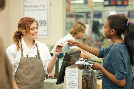 Female shop assistant handing bill to customer Stock Photo - Premium Royalty-Free, Code: 649-07119190
