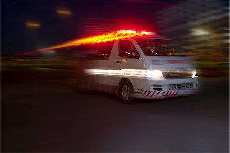 sin autorización de la propiedad - Emergency ambulance speeding through city at night Foto de stock - Sin royalties Premium, Código: 649-07119215