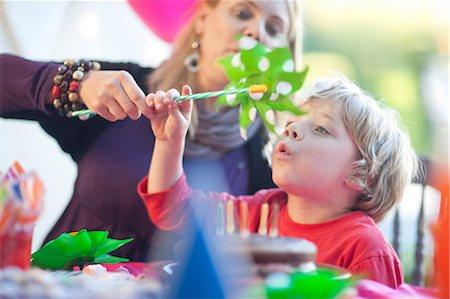 Young boy blowing windmill at birthday party Stock Photo - Premium Royalty-Free, Code: 649-07119293