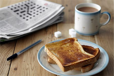 sweet   no people - Kitchen table still life with crossword, toast and tea Stock Photo - Premium Royalty-Free, Code: 649-07119300