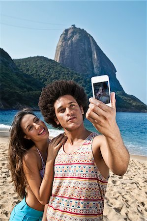 Couple photographing themselves on beach with camera phone, Rio de Janeiro, Brazil Stock Photo - Premium Royalty-Free, Code: 649-07119347