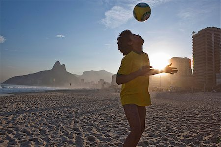 Young man heading football, Ipanema Beach, Rio, Brazil Stock Photo - Premium Royalty-Free, Code: 649-07119413