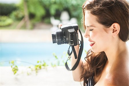 Young woman looking through camera viewfinder Stock Photo - Premium Royalty-Free, Code: 649-07119501