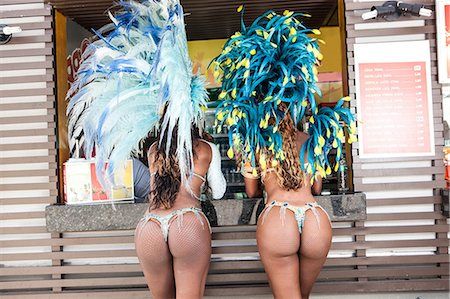 Rear view of samba dancers in costume by food stall, Rio De Janeiro, Brazil Stock Photo - Premium Royalty-Free, Code: 649-07119518