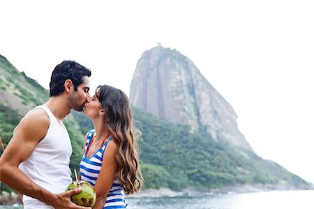 Couple kissing on beach with Sugarloaf Mountain, Rio de Janeiro, Brazil Stock Photo - Premium Royalty-Free, Code: 649-07119653