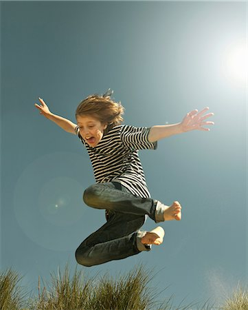 Teenage boy jumping against clear blue sky Stock Photo - Premium Royalty-Free, Code: 649-07119689