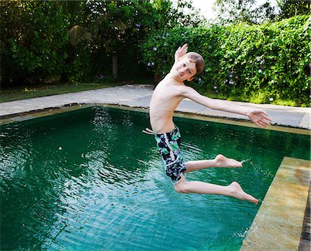 Boy jumping into swimming pool Stock Photo - Premium Royalty-Free, Code: 649-07119725