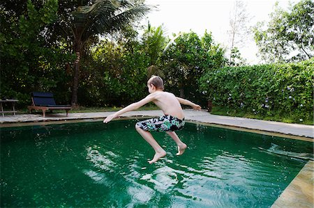 Boy jumping into swimming pool Stock Photo - Premium Royalty-Free, Code: 649-07119727