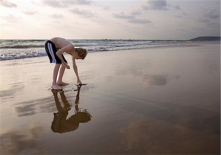 Boy bending over touching sand on beach Stock Photo - Premium Royalty-Free, Code: 649-07119736