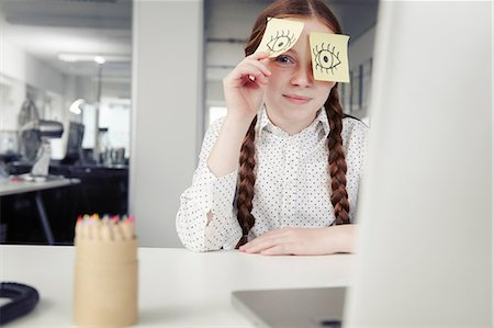 self adhesive note - Girl in office with adhesive notes covering eyes, peeking Stock Photo - Premium Royalty-Free, Code: 649-07119764