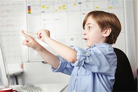 Boy playing with elastic band in office Stock Photo - Premium Royalty-Free, Code: 649-07119778