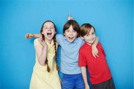 Portrait of three children with arms around each other against blue background Stock Photo - Premium Royalty-Free, Code: 649-07119796