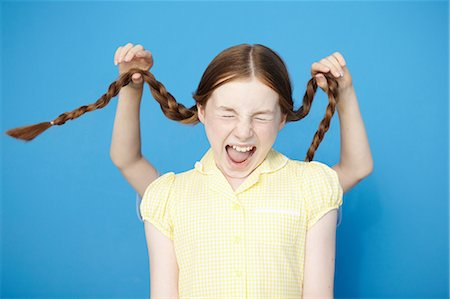 preteen open mouth - Girl wearing yellow school dress, boy behind pulling her plaits Stock Photo - Premium Royalty-Free, Code: 649-07119802
