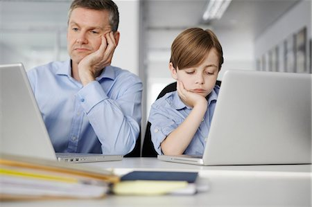 Father and son using laptops looking bored Stock Photo - Premium Royalty-Free, Code: 649-07119816