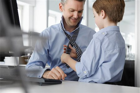 father with two sons not girls - Son putting tie on father at desk Stock Photo - Premium Royalty-Free, Code: 649-07119813