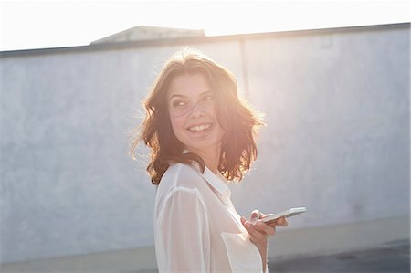 Portrait of young woman holding cell phone in sunlight Stock Photo - Premium Royalty-Free, Code: 649-07119920