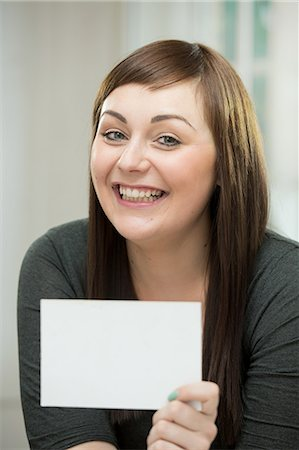 Happy young woman with a blank card Stock Photo - Premium Royalty-Free, Code: 649-07238233