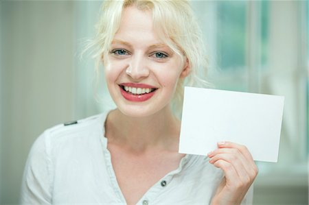 Young woman holding a blank card Stock Photo - Premium Royalty-Free, Code: 649-07238264