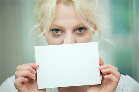 Young woman holding a blank card over her face Stock Photo - Premium Royalty-Free, Code: 649-07238265