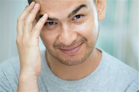 Mid adult man touching his face Stock Photo - Premium Royalty-Free, Code: 649-07238274
