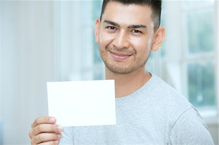 Mid adult man holding a blank card Stock Photo - Premium Royalty-Free, Code: 649-07238273