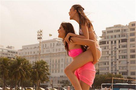 Young woman riding piggyback on friend, Copacabana Beach, Rio De Janeiro, Brazil Stock Photo - Premium Royalty-Free, Code: 649-07238320
