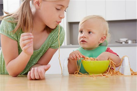 Girl and toddler playing with spaghetti Stock Photo - Premium Royalty-Free, Code: 649-07238337