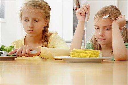 sad child sitting - Girls poking vegetables on plate Stock Photo - Premium Royalty-Free, Code: 649-07238340