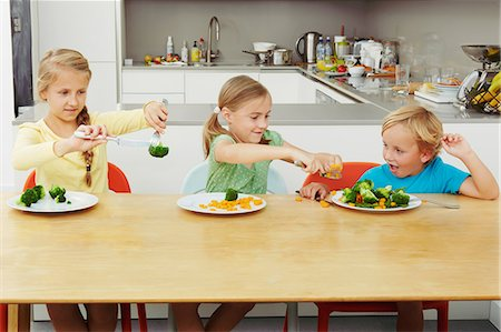 Girls scooping vegetables onto boy's plate Stock Photo - Premium Royalty-Free, Code: 649-07238341