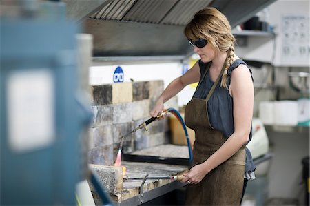 Woman wearing safety goggles using blowtorch for metalworking Stock Photo - Premium Royalty-Free, Code: 649-07238385