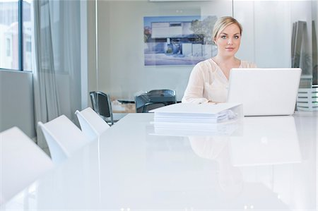 Woman sitting at conference room table using laptop Stock Photo - Premium Royalty-Free, Code: 649-07238396