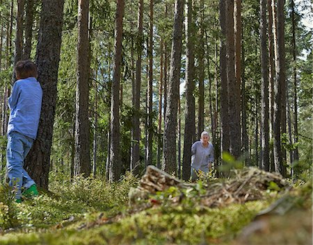 Mother and son playing hide and seek in forest Stock Photo - Premium Royalty-Free, Code: 649-07238461