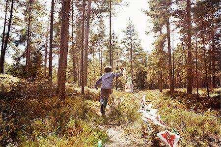 Boy running through forest pulling bunting Stock Photo - Premium Royalty-Free, Code: 649-07238471