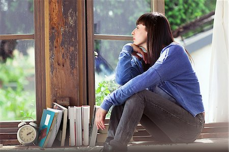 Woman sitting on windowsill Stock Photo - Premium Royalty-Free, Code: 649-07238510