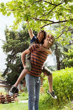 reaching - Man giving woman piggy back in orchard Stock Photo - Premium Royalty-Free, Code: 649-07238535
