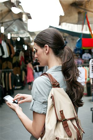 Young woman texting on cell phone, San Lorenzo market, Florence, Tuscany, Italy Stock Photo - Premium Royalty-Free, Code: 649-07238567